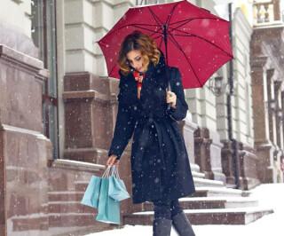 Frau mit rotem Regenschirm und Einkaufstüten im Schnee