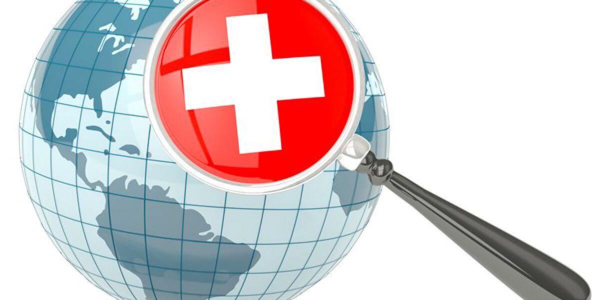 Globus und Lupe mit dem Symbol der Schweiz