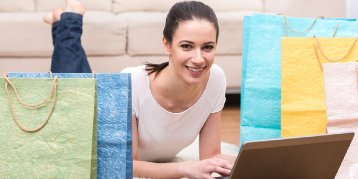 Frau liegt auf dem Boden umgeben von Shopping-Tüten und surft im Internet