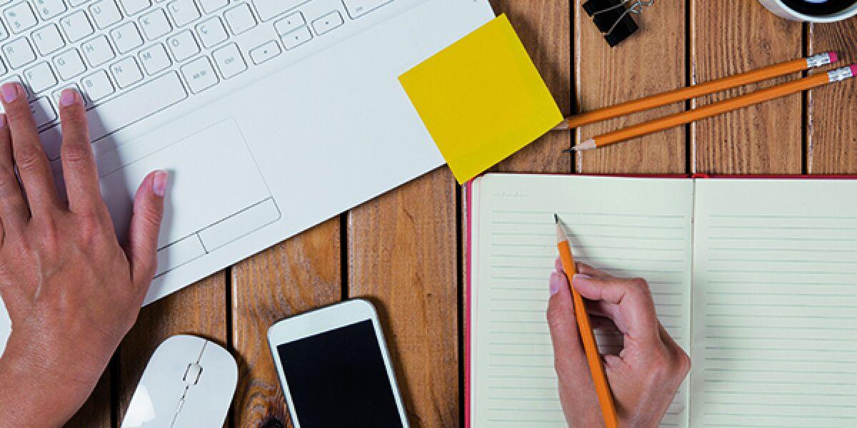 Schreibtisch Hand schreibt Notebook