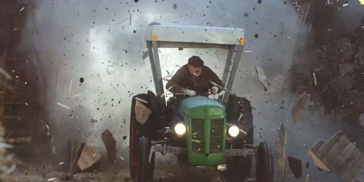Mann fährt mit Traktor durch Scheunentor