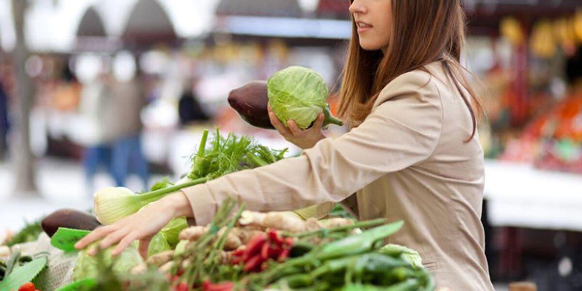 Frau kauft Gemüse ein