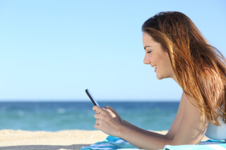 Frau am Strand mit Handy