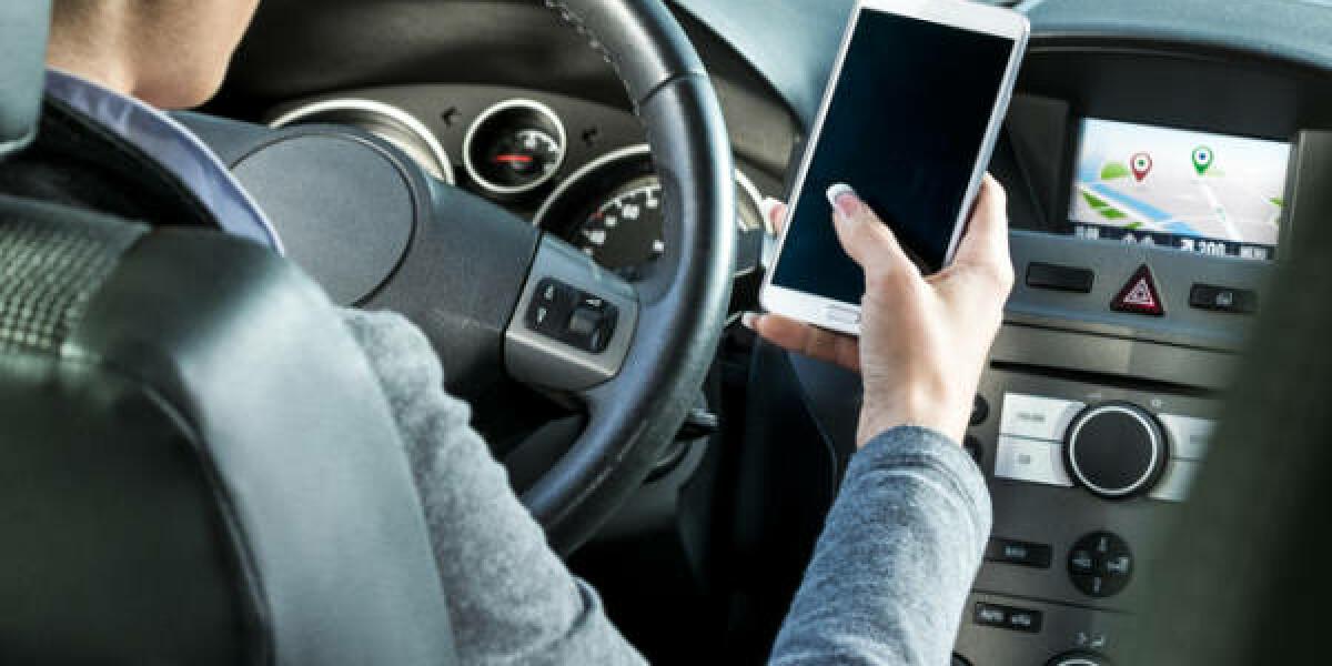 Frau hält im Auto ihr Smartphone in der Hand