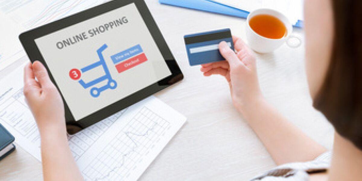 Frau hält Tablet und Kreditkarte in der Hand