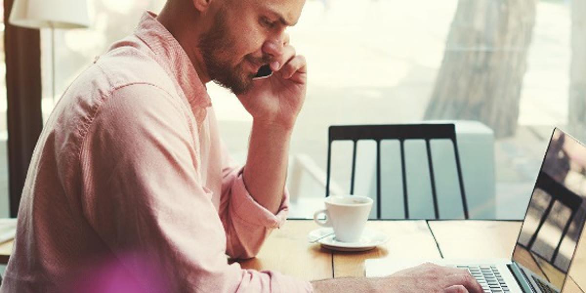 Ein Mann sitzt am Laptop und telefoniert