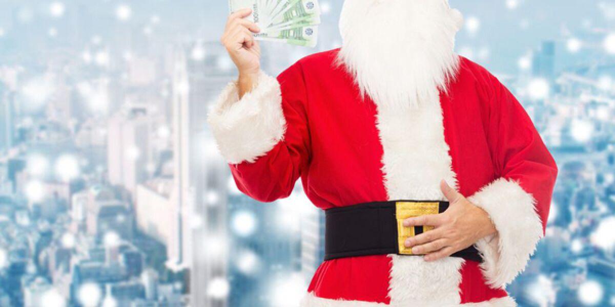 Weihnachtsmann mit Geldscheinen in der Hand