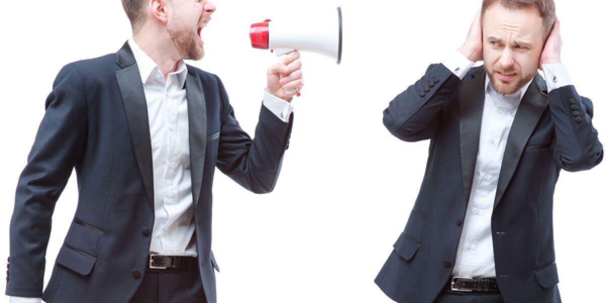 Mann mit Megaphon schreit anderen an, der hält sich die Ohren zu