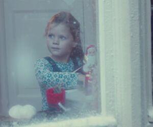 Mädchen steht am Fenster