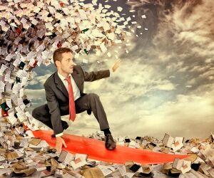 Mann im Anzug surft auf Welle aus Geldscheinen