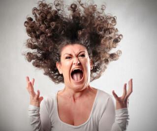 Frau schreit vor Wut und ihr stehen die Haare zu Berge