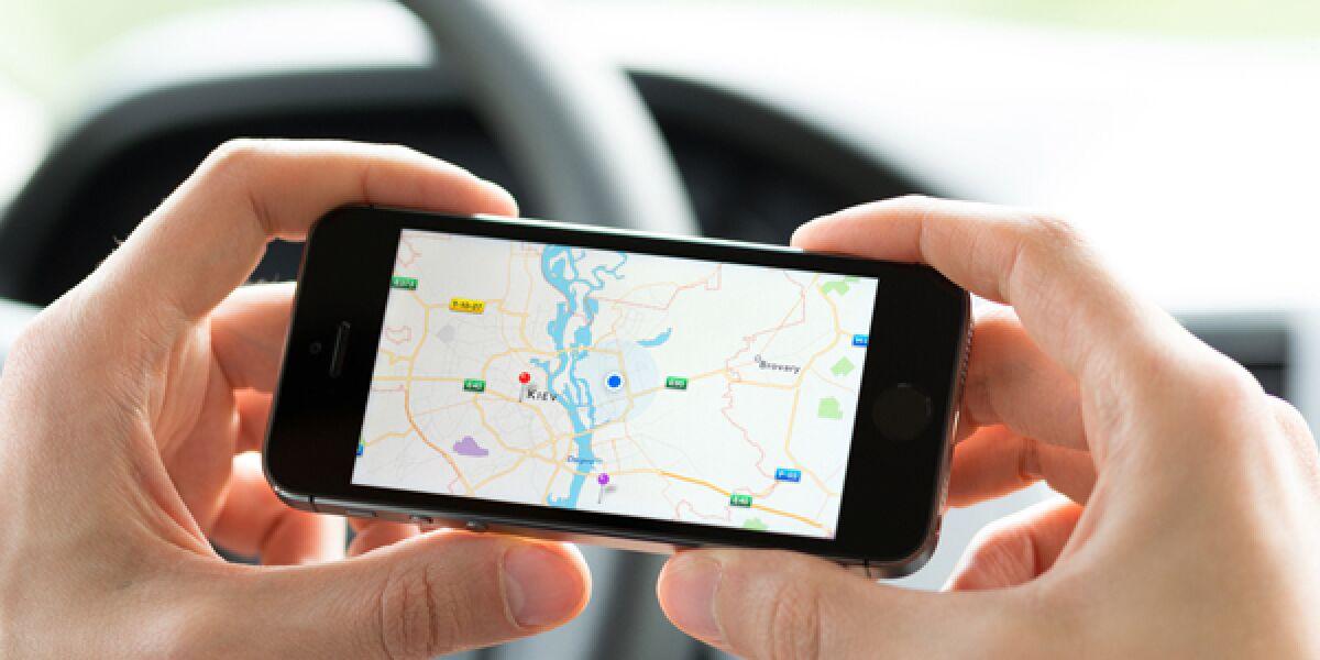 Autofahrer mit Handy und Maps