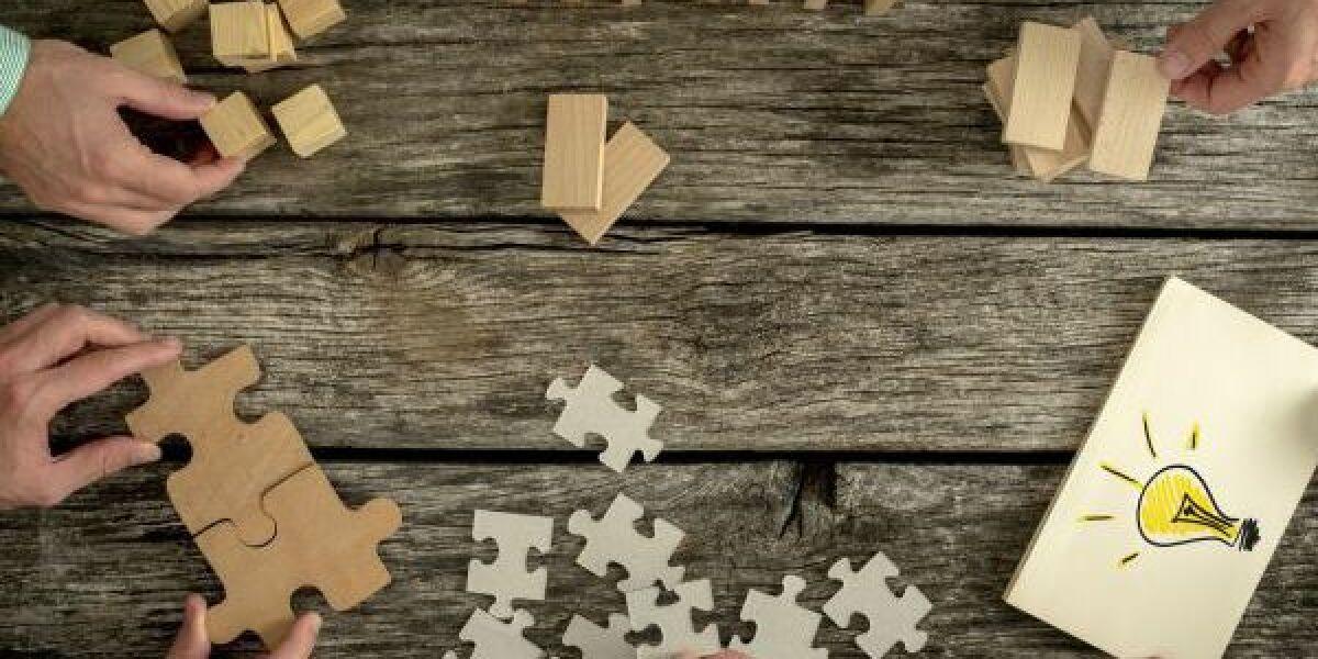Hände lösen Puzzle aus Holz