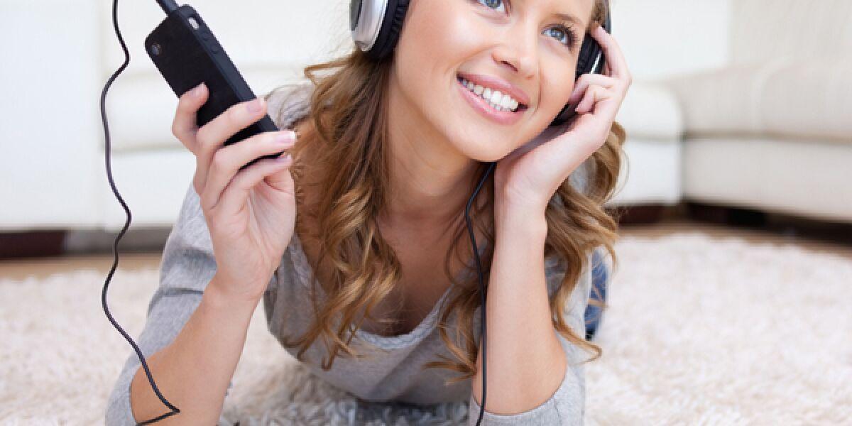 Frau hört mit Köpfhörer Musik