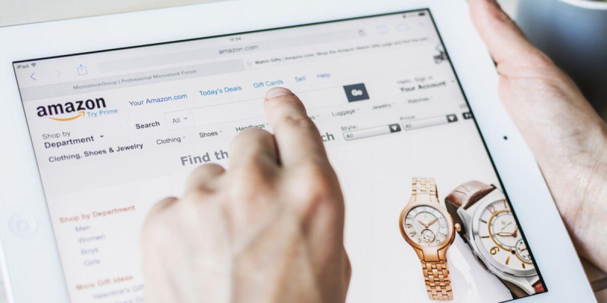 Hand mit Tablet und Amazon