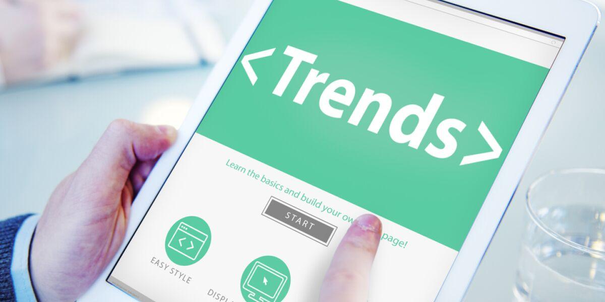 Mann hält Tablet mit Trends