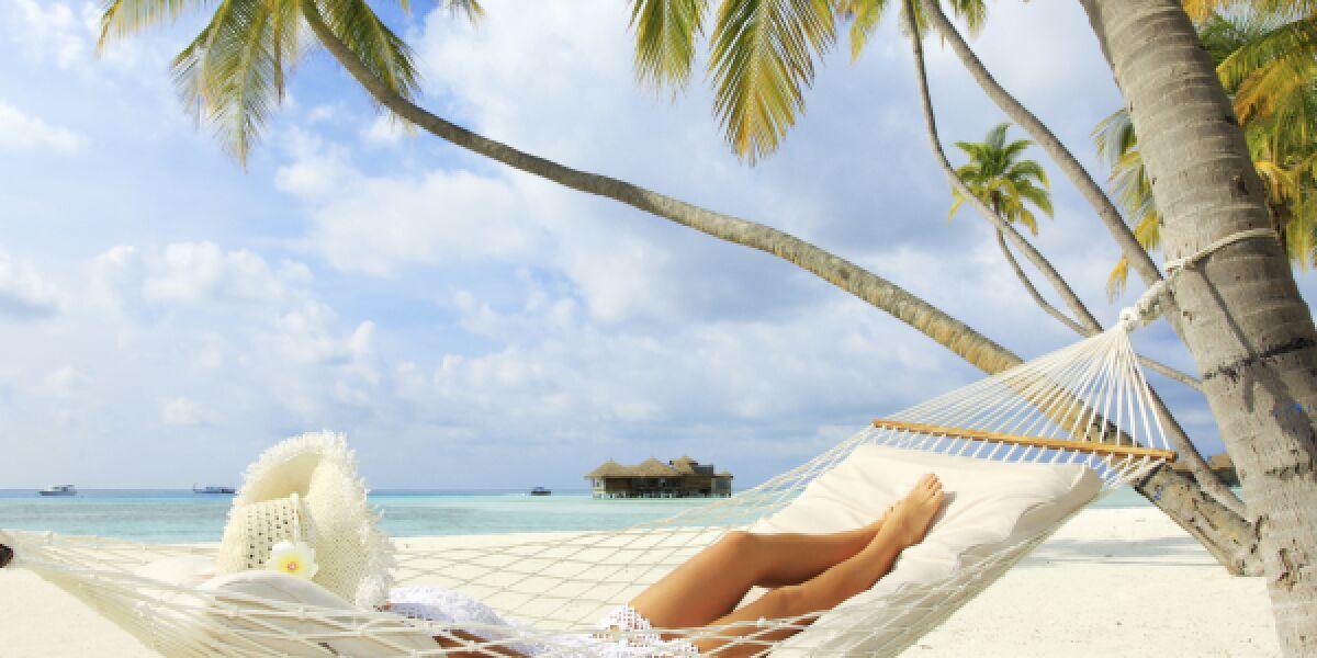 Eine Frau liegt am Strand in einer Hängematte