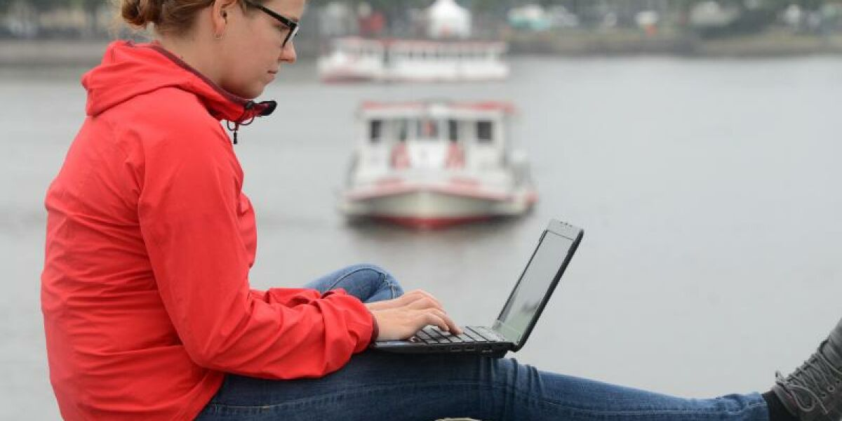 Frau surft mit Laptop an der Binnenalster