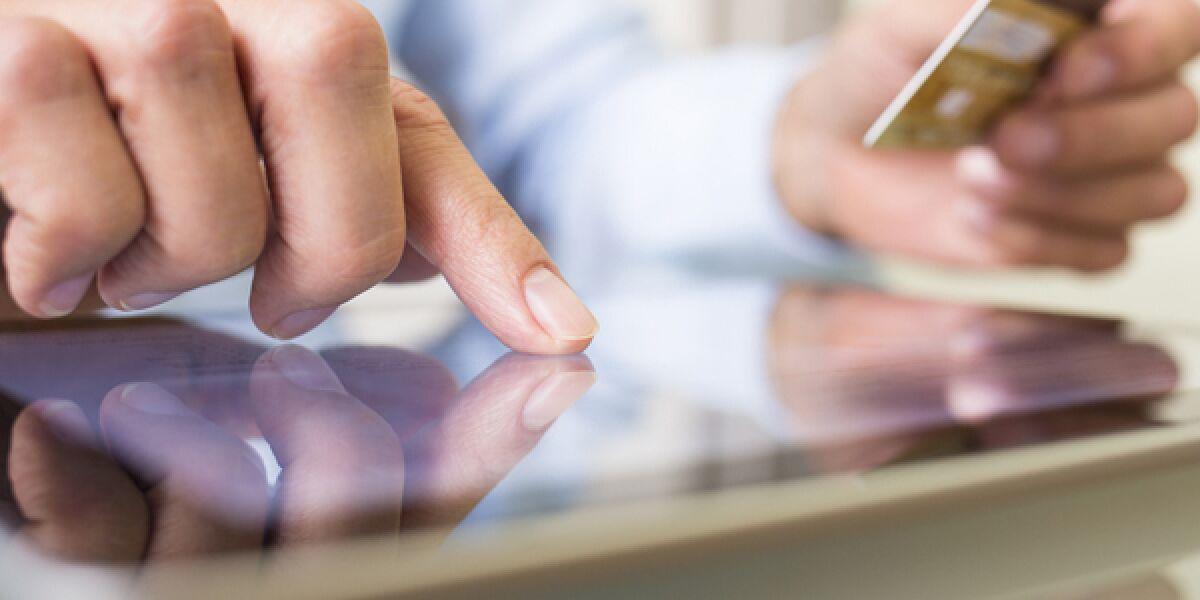 Mann am Tablet mit Kreditkarte in der Hand