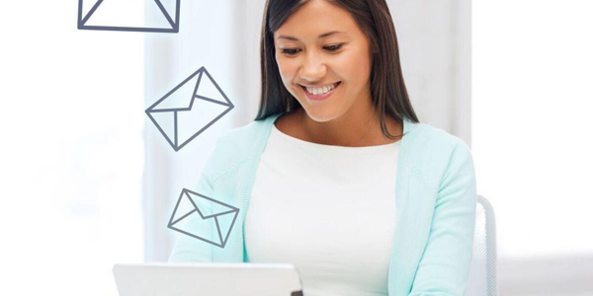 Frau sitzt am Laptop und liest E-Mails