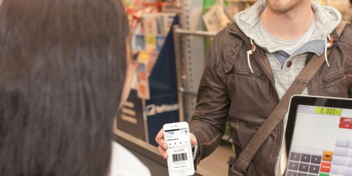 Mann steht mit Smartphone in der Hand an der Kasse