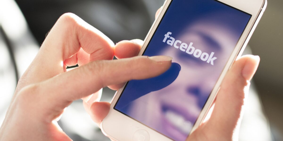 Frau hält ein Smartphone mit der Facebook App in der Hand