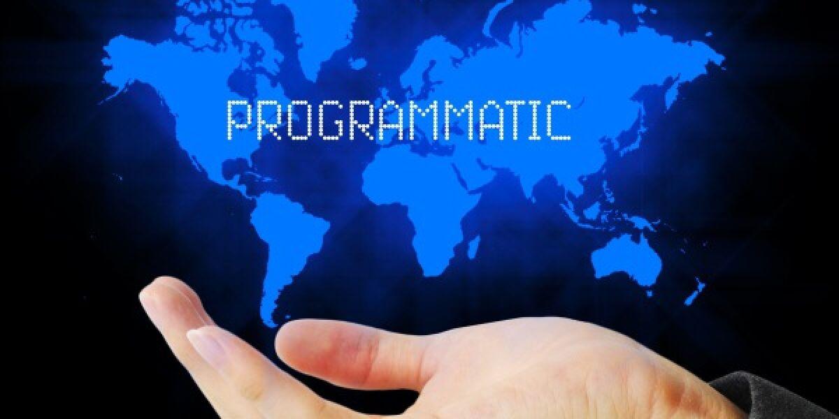 Hand unter Weltkarte auf der Programmatic steht