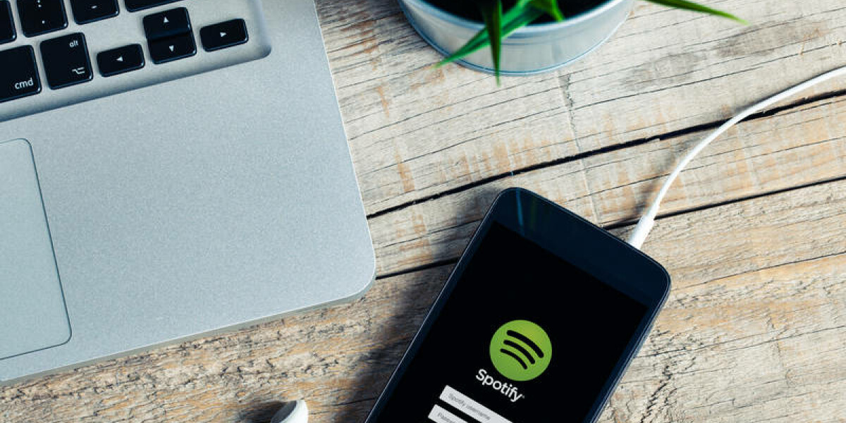 Smartphone mit Spotify-App neben Laptop