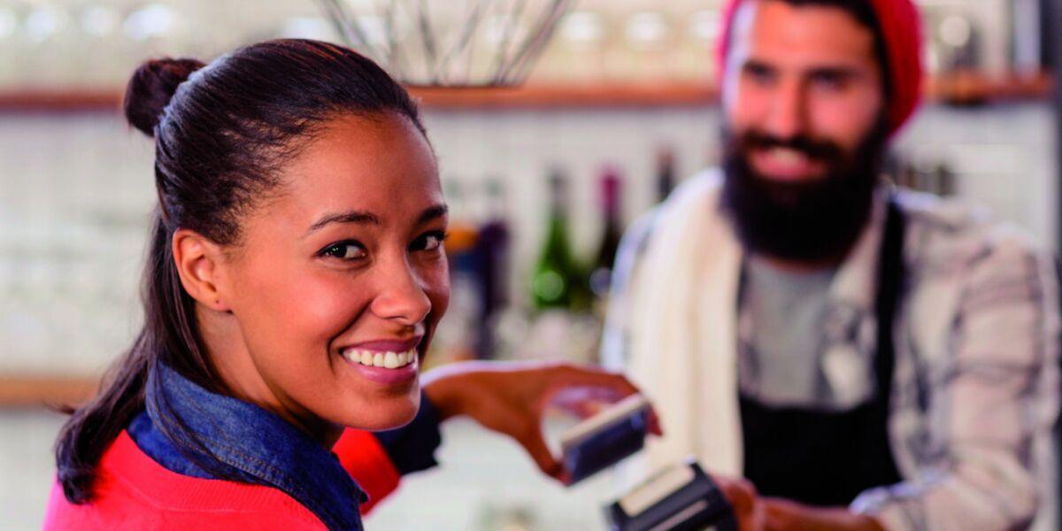 Mobile-Payment Frau zahlt mit Smartphone im Laden