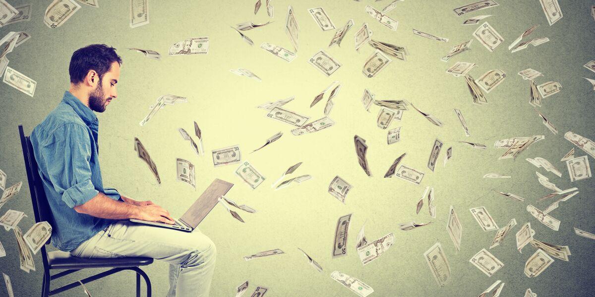 Geldscheine fliegen um Mann mit Computer