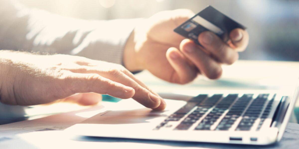 Mann am Laptop mit Bankkarte in der Hand