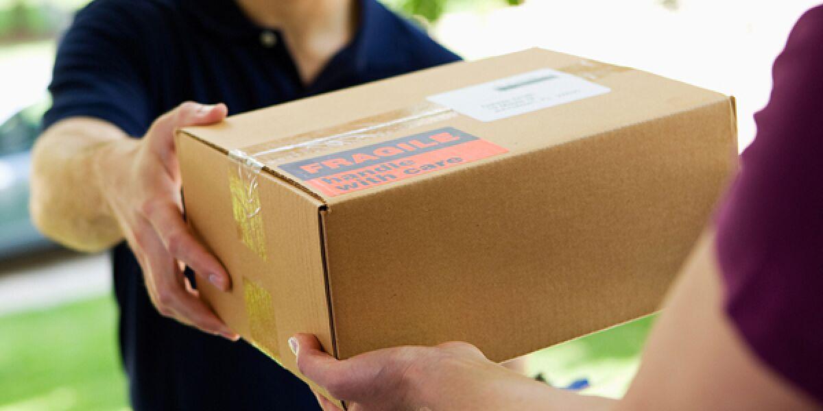 Mann gibt einer Frau an der Tür ein Paket