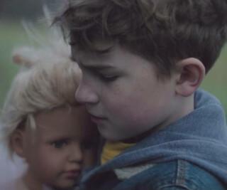 Junge mit einer Puppe im Arm