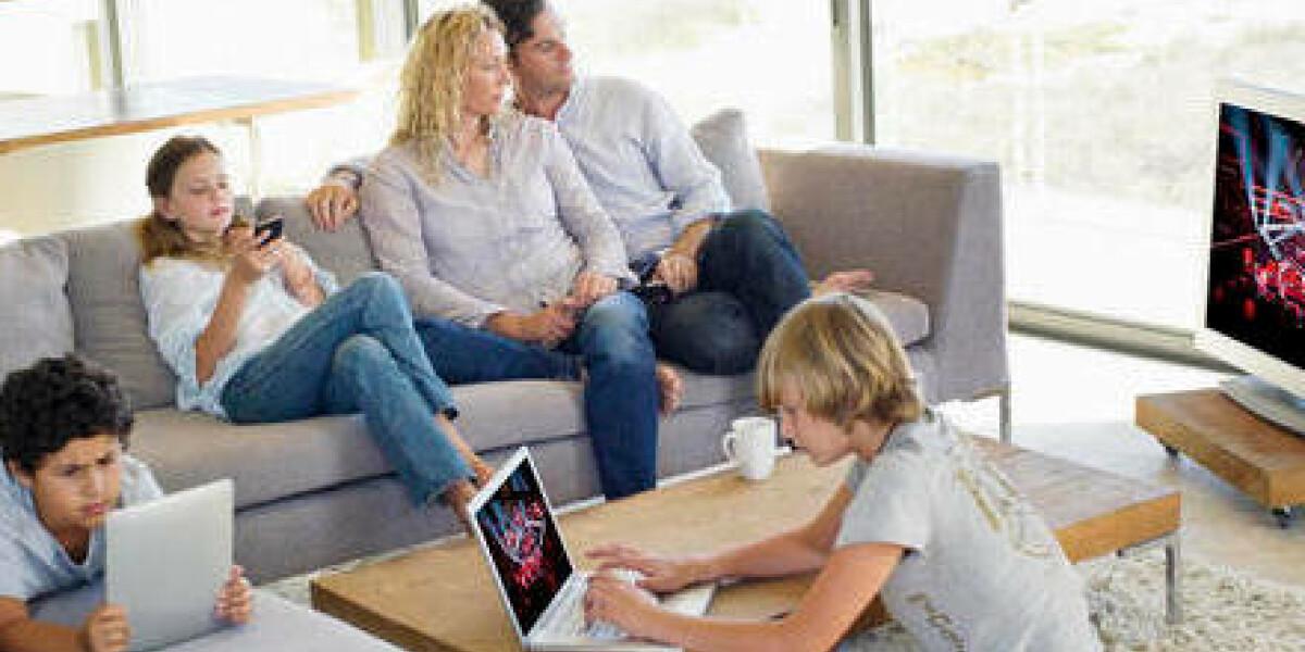 Familie schaut fernsehen, kinder spielen nebenbei am Smartphone oder Tablet