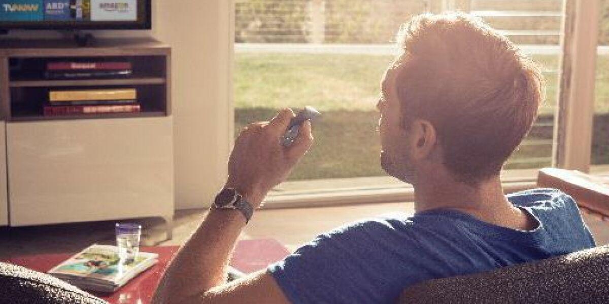 Mann sitzt auf dem Sofa vor dem Fernseher