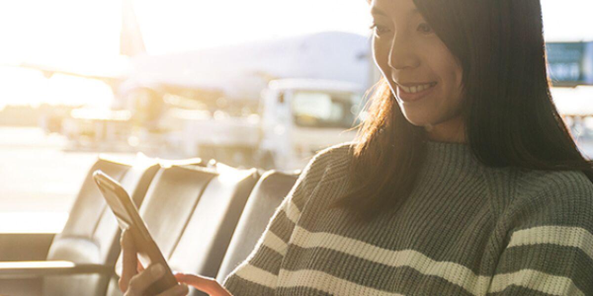 Frau sitzt am Flughafen mit einem Smartphone in der Hand
