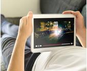 Mann liegt auf dem Sofa und schaut Film auf Tablet