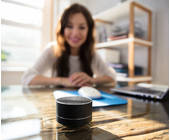 Frau sitzt vor smartem Speaker