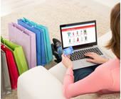 Frau sitzt mit einem Laptop auf einem Sofa