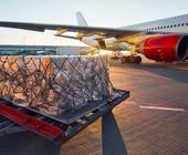 Kartons stehen vor einem Flugzeug