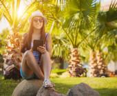 Frau sitzt unter Palmen mit einem Tablet in der Hand