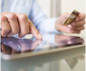 Mann bedient Tbalet und hält Kreditkate in der anderen Hand