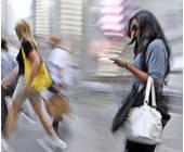 Frau unterwegs mit Smartphone in der Hand