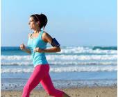 Frau joggt am Meer mit Smartphone