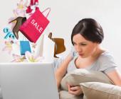 Frau liegt vor dem Laptop und shoppt online