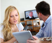 Mann und Frau mit Fernseher und Tablet