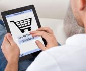 Mann shoppt auf Sofa mit Tablet