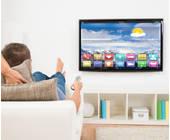 Mann liegt auf dem Sofa und blickt in den Fernseher