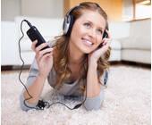 Frau liegt auf dem Boden und hört mit Handy Musik