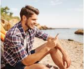 Ein Mann sitzt mit Smartphone in der Hand am Strand